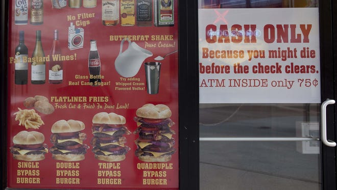 Menu offerings and warnings are posted in the window of the Heart Attack Grill on Fremont Street, on  Feb. 15, 2012, in Las Vegas.