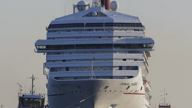 The Carnival Triumph is towed into Mobile Bay near Dauphin Island, Ala., on Thursday. The ship with more than 4,200 passengers and crew members has been idled for nearly a week in the Gulf of Mexico following an engine room fire.