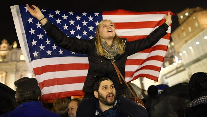 A girl waves a U.S. flag in Vatican City. With the election of a new pope, more Americans could be heading to Rome soon.