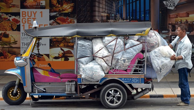 A Thai worker loads packs of clothes into a tuk-tuk at shopping mall in Bangkok. The city is forecast to be the world's No. 1 destination in terms of visitor arrivals in 2013.