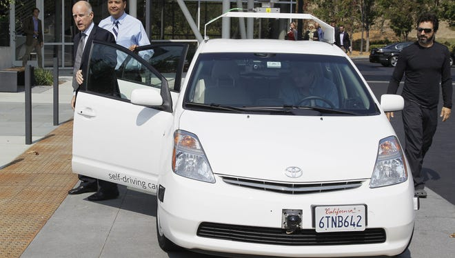 From left, California Gov. Edmund G Brown Jr., state Senator Alex Padilla and Google co-founder Sergey Brin stand by a driverless car they arrived in at Google headquarters in Mountain View, Calif.
