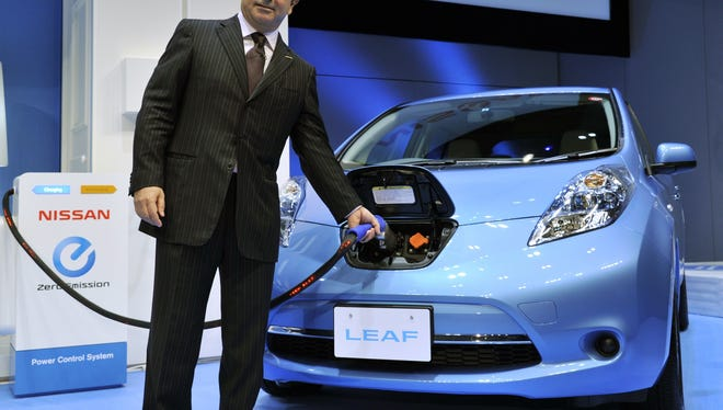 """Japan's auto Nissan president Carlos Ghosn charges the electric vehicle """"Leaf"""" during an announcement of the the company's new mid-term environment plan at their headquarters in Yokohama, suburban Tokyo on October 24, 2011"""