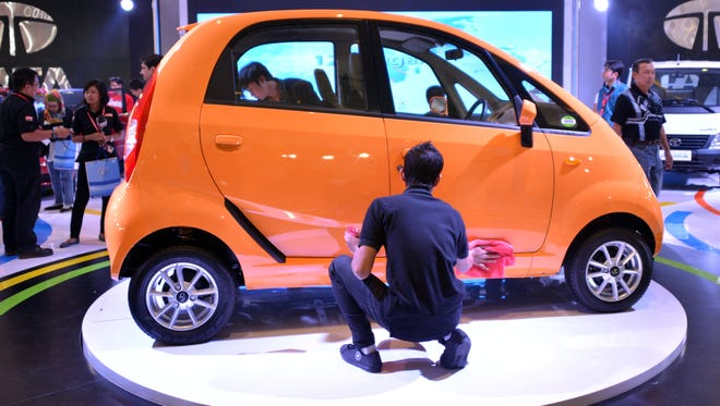 Workers wipe the low-cost Nano car manufactured by Tata of India.