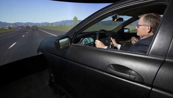 Dr. E. Gordon Gee, president, The Ohio State University, tests new driving simulator.