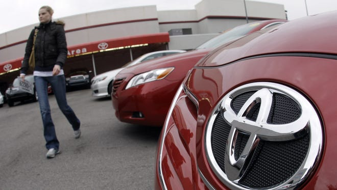 A customer walks past a new Toyota Camry at a dealership in this 2010 file photo