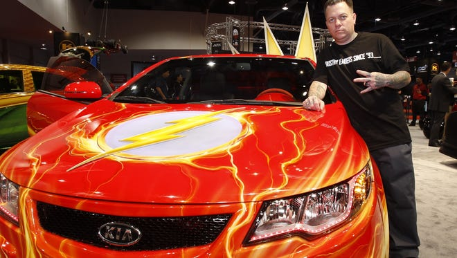 Ryan Friedlinghaus shows off the Flash inspired KIA Forte Koupe as part of the Justice League  super heroes themed cars  during the  SEMA convention in Las Vegas
