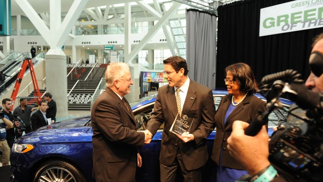 Green Car Journal editor Ron Cogan, left, presents the Green Car of the Year award to Dave Mondragon, Ford general marketing manager, at the Los Angeles Auto Show