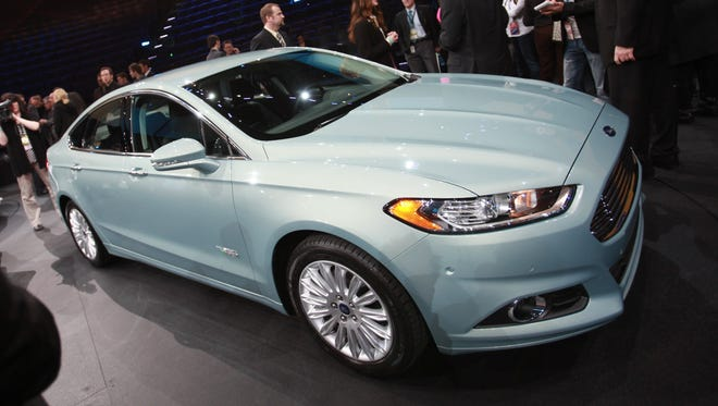 Reporters surrounds the 2013 Fusion Energi at the North American International Auto Show at Cobo Center in Detroit.