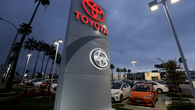 A Toyota dealership signs glows over a car lot in Tustin Calif.