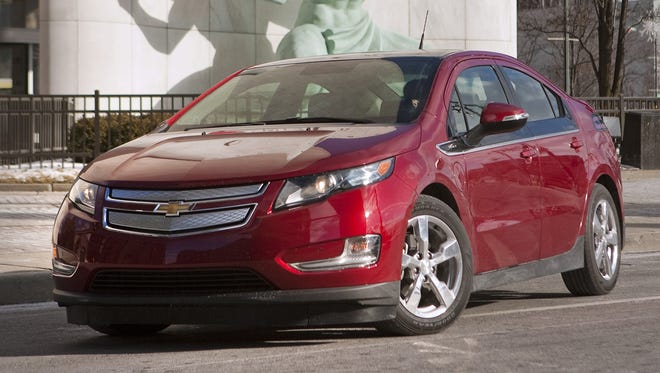 The Chevrolet  Volt is pictured in front of the Spirit of Detroit statue.