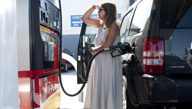 Teresa Jones watches the pump as she puts gas into her car at a Shell station on Pico Blvd in Los Angeles last year