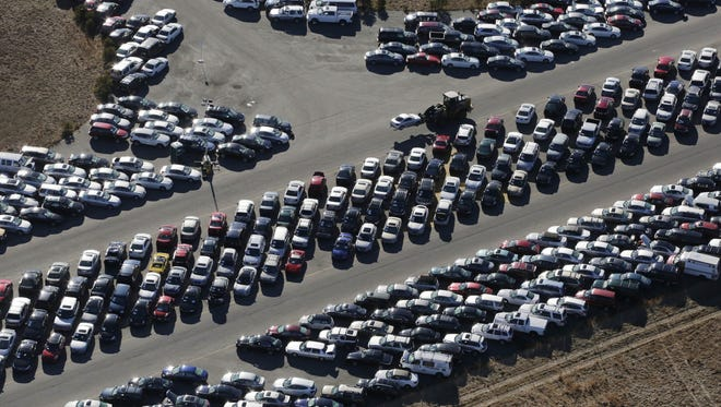 In this Jan. 18 aerial photo, a forklift moves a car for storage among the thousands of vehicles which were damaged in Superstorm Sandy and stored on the runways at Calverton Executive Airpark in Calverton, N.Y.