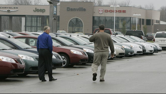 Two men talk as they walk on a car dealer lot in Avon, Ind., in this 2008 file photo.