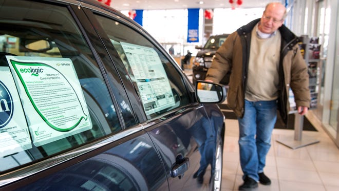 Ronald Sill of Commerce Township., Mich., walks around the Chevrolet Malibu while looking to buy a new vehicle