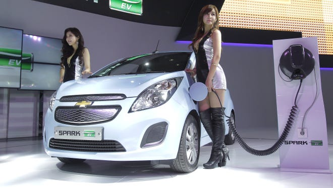 Models pose next to a Chevrolet Spark EV at the Seoul Motor Show 2013