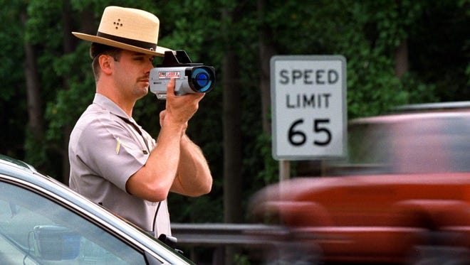Maryland State Trooper Mark Dillon operates laser gun speed trap near Annapolis, Md., on Interstate 97 in this 1997 file photo