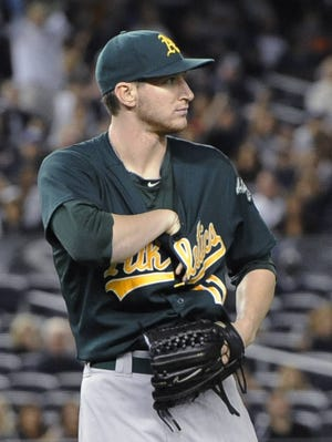A's starter Jarrod Parker reaches down his shirt to grab a baseball that went inside it on an infield single by the Yankees' Ichiro Suzuki.