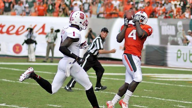 Miami (Fla.) wide receiver Phillip Dorsett hauls in a catch for a touchdown as North Carolina State cornerback David Amerson defends during the fourth quarter at Sun Life Stadium.