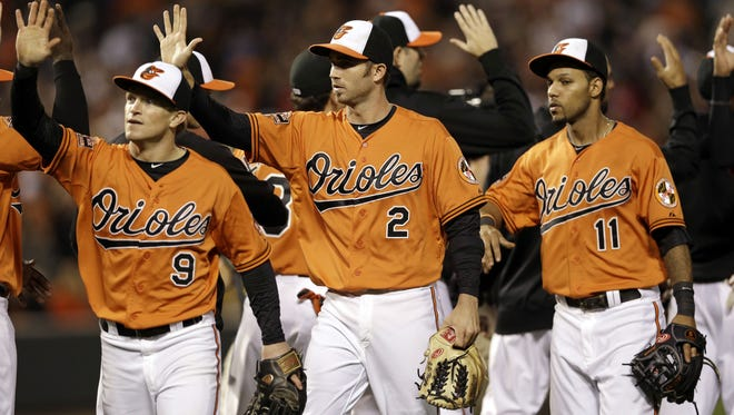 Baltimore Orioles players (L-R) Nate McLouth, J.J. Hardy and Robert Andino celebrate a win over the Boston Red Sox over the weekend that pulled them into a tie in the AL East race and moved them closer to a playoff spot.