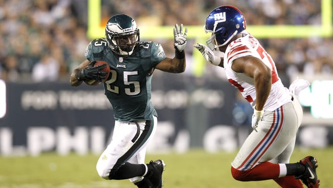 Philadelphia Eagles running back LeSean McCoy (25) runs with the ball as New York Giants defensive end Osi Umenyiora (72) defends on the play during the first half of an NFL football game Sunday, Sept. 30, 2012.