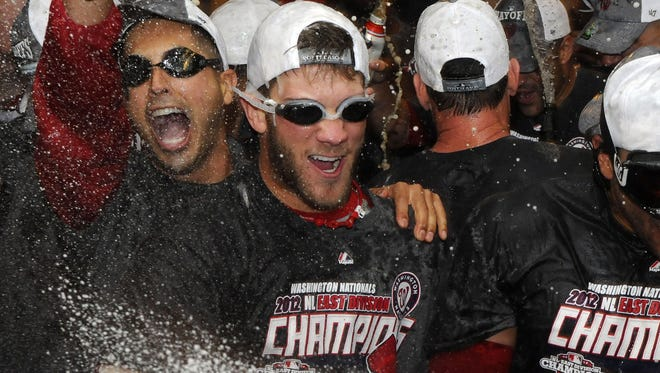 The Nationals's 19-year-old outfielder Bryce Harper (center) celebrates after Washington clinched the National League East title at Nationals Park.