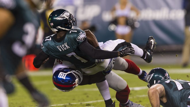 New York Giants defensive end Justin Tuck (91) takes down Philadelphia Eagles quarterback Michael Vick (7) during the first quarter  at Lincoln Financial Field.
