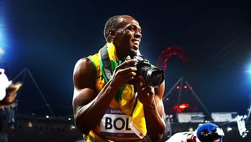 Usain Bolt takes pictures with the camera up for auction.