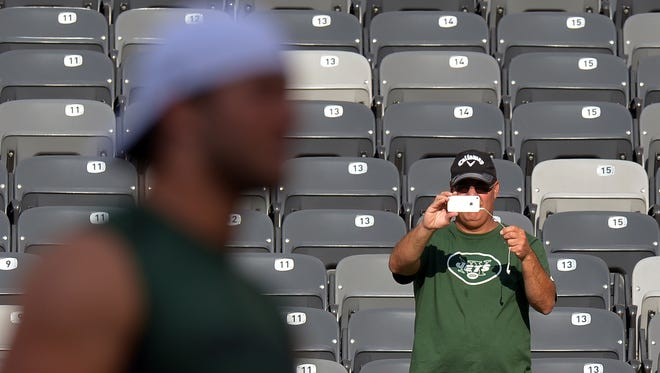 A fan uses a smartphone to photograph Tim Tebow of the New York Jets as he walks across the field before the game against the New York Giants at MetLife Stadium in August.