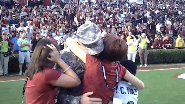 Sgt. 1st Class Scott Faile hugs his family after a surprise reunion prior to kickoff between South Carolina and Georgia.