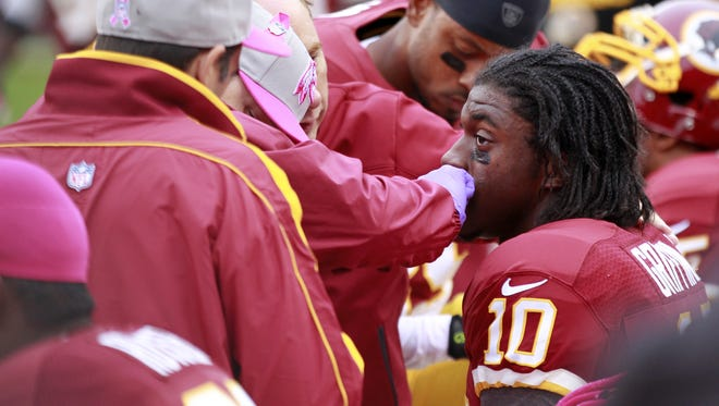 Trainers work on Robert Griffin III after he was knocked out of the game on Sunday.