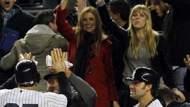 Fans cheer as New York Yankees third baseman Alex Rodriguez (center) welcomes first baseman Mark Teixeira (25) back to the dugout during Game 1 of the 2012 ALCS against the Detroit Tigers at Yankee Stadium.  Fans Kyna Treacy (red coat) and Kate Quinn (right of Treacy) cheer the play.
