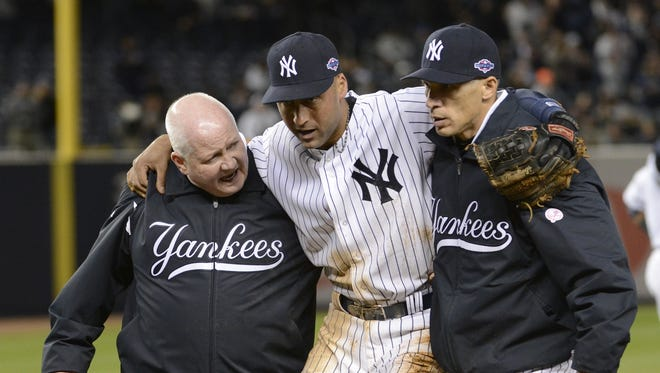 Yankees shortstop Derek Jeter, center, is taken off the field by trainer Steve Donohue and manager Joe Girardi, right, in Game 1 of the ALCS.