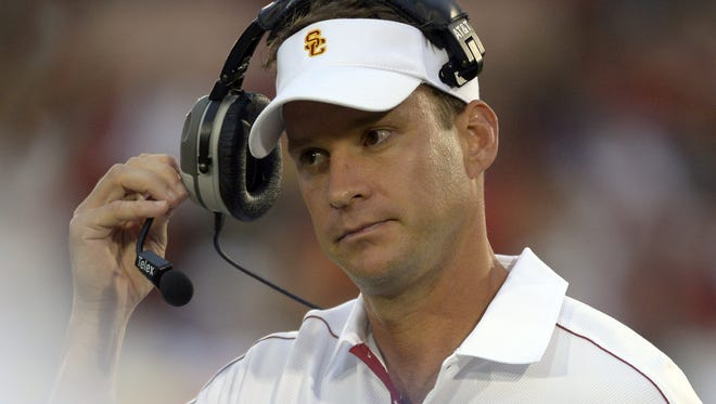 USC head coach Lane Kiffin takes off his headset during the Trojans' 50-6 win over Colorado on Oct. 20.
