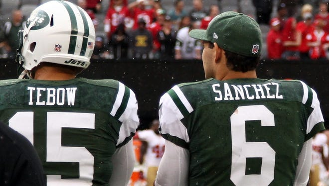 New York Jets quarterback Tim Tebow (15) and quarterback Mark Sanchez (6) on the sidelines against the San Francisco 49ers during the second half at MetLife Stadium.