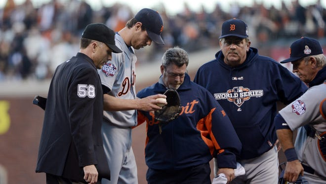Tigers pitcher Doug Fister (second from left) is checked on by trainer Kevin Rand (middle) after being struck in the head with a batted ball in the second inning of Game 2.