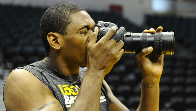 Lakers forward Metta World Peace takes pictures of teammates practicing prior to the Lakers preseason game against the Sacramento Kings on Thursday.