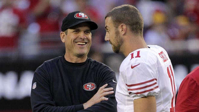 49ers quarterback Alex Smith (11) talks with coach Jim Harbaugh during warm-ups prior to Monday night's game against the Cardinals.