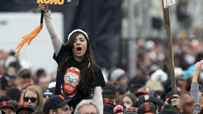 A fan holds up a Sergio Romo sign with a shirt feting Brian Wilson at the Giants' victory parade in San Francisco.