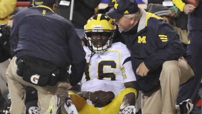 Michigan quarterback Denard Robinson is looked over by Michigan staff members after suffering an injury against Nebraska on Oct. 27.