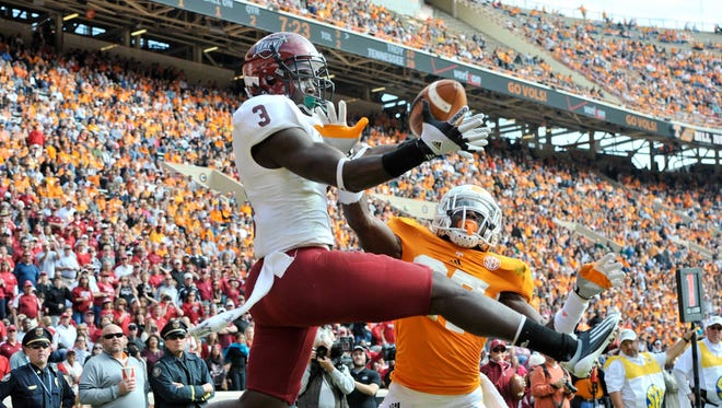 Troy wide receiver Eric Thomas pulls in a pass against Tennessee defensive back Justin Coleman during the first half of a 55-48 UT win.