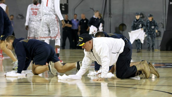 Head coach Buzz Williams (white jacket) of the Marquette Golden Eagles helps dry condensation off of the court, which caused the start of their game.