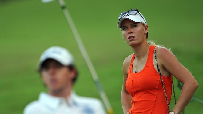 Tennis star Caroline Wozniacki watches her boyfriend  Rory McIlroy  play a shot during the  first round of the Barclays Singapore Open two weeks ago.