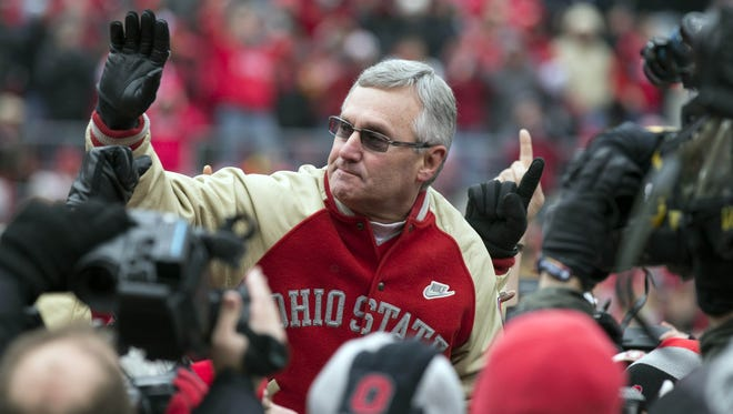 Ohio State Buckeyes former coach Jim Tressel is held by players from his 2002 National Championship team in a game against the Michigan Wolverines at Ohio Stadium.