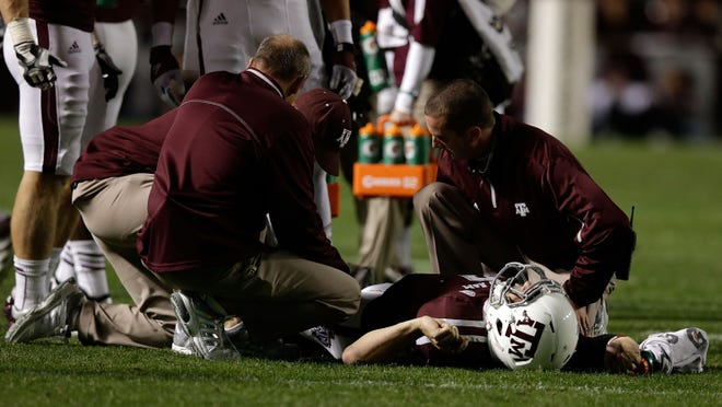 Texas A&M quarterback Johnny Manziel has his knee looked at by doctors after being tackled against Missouri.