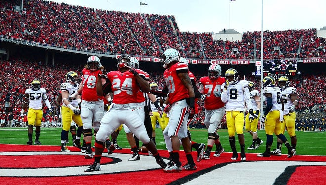 Ohio State running back Carlos Hyde, middle, celebrates after scoring a touchdown in the first quarter. The Buckeyes beat the Michigan Wolverines 26-21.