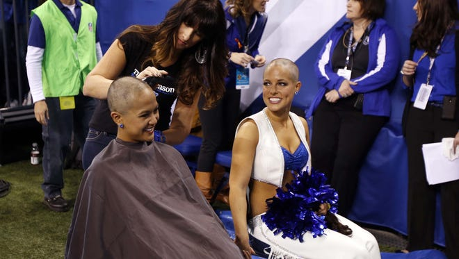 Megan M. (right) and Crystal B. shave their heads after meeting fundraising goal.