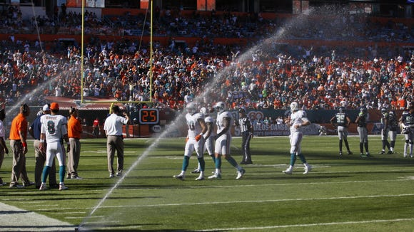 Sprinklers come on during Dolphins game, soaks players