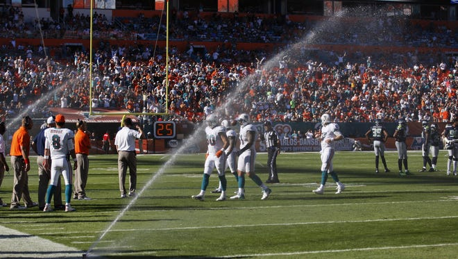 Sprinklers come on during the second half of an NFL football game between the Miami Dolphins and Seattle Seahawks.