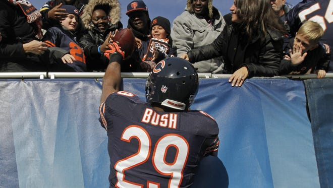 Chicago Bears running back Michael Bush (29) gives a ball to a fan after making a touchdown run in the first half of an NFL football game against the Minnesota Vikings in Chicago.