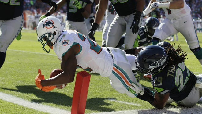 Miami Dolphins running back Reggie Bush (22) stretches for a touchdown as Seattle Seahawks  Earl Thomas (29) attempts to tackle him during the first half of an NFL football game Sunday, Nov. 25, 2012 in Miami